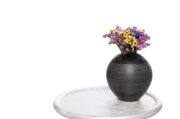 白い背景の上の黒い花瓶のリモニウムの美しい花束