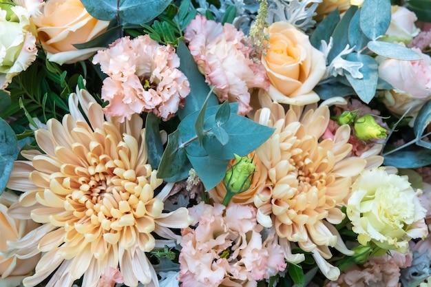 木製のテーブルの上の花瓶に混合花の美しい花束。フラワーショップでの花屋の仕事。ひまわり、菊、バラの鮮やかなミックス。