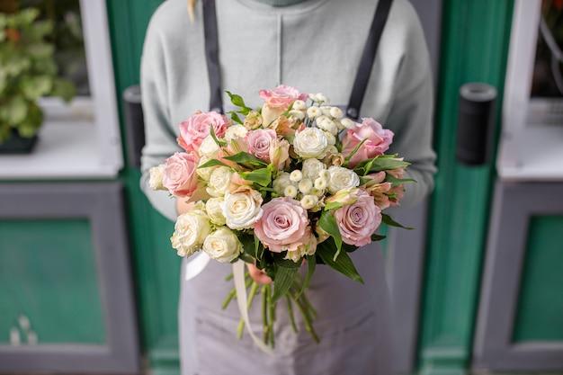 女性の手で混合花の美しい花束。花屋