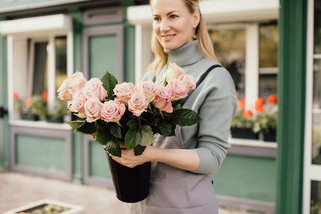 女性の手で混合花の美しい花束。