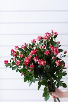 バラと混合花の美しい花束。花屋の仕事。花の配達。