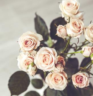 黒にヴィンテージの花瓶の桃のバラの美しい花束