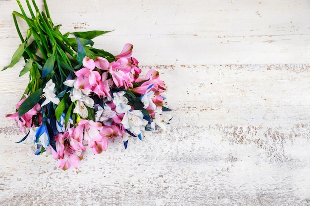 흰색 나무 바탕에 분홍색과 파란색 alstroemerias의 아름 다운 꽃다발.