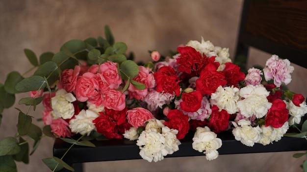 ピンクと白のカーネーションの美しい花束。緑の小枝の花束は、暗いテクスチャの背景にあります