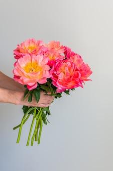 Красивый букет розовых пионов в мужской руке на фоне белой стены