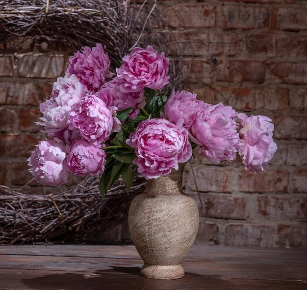 꽃병에 분홍색 모란의 아름 다운 꽃다발입니다. 정물 실내