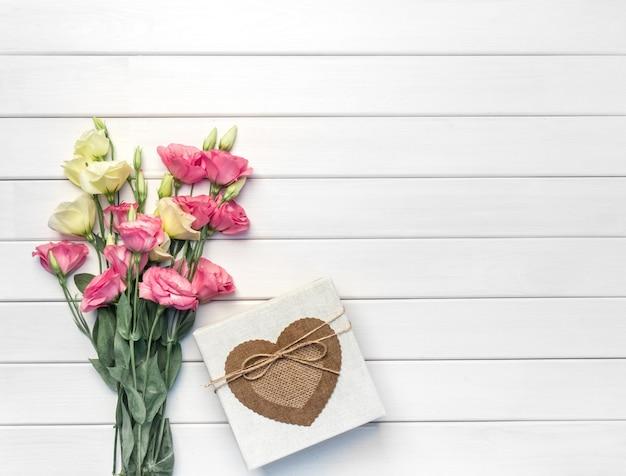 ピンク、紫、黄色のトルコギキョウの花と白い木製の手作りギフトボックスの美しい花束