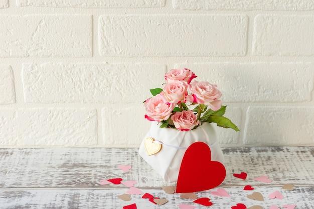 Красивый букет из розовых роз и красных сердечек. любовная композиция на свадьбу или день святого валентина.