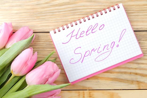 ピンクのチューリップの花の美しい花束と自然な木の表面のノートにテキストこんにちは春