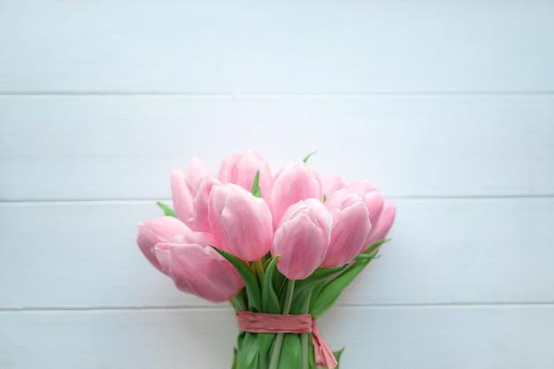 흰색 나무 바탕에 분홍색 튤립의 아름다운 꽃다발.