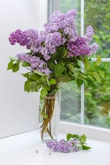 Красивый букет фиолетовой сирени в стеклянной вазе на белом подоконнике