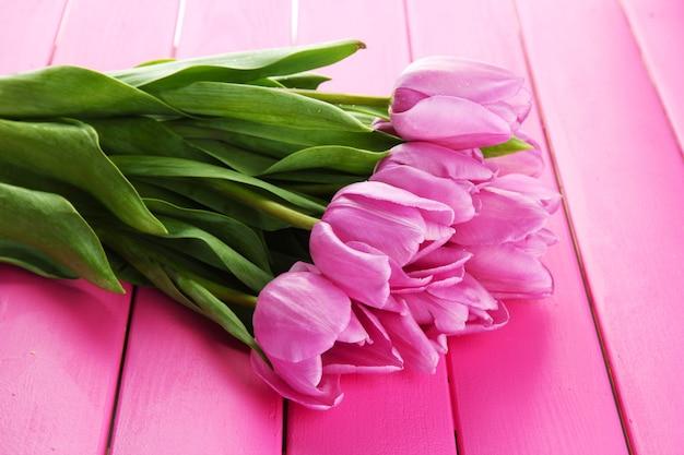 ピンクの木の表面に紫色のチューリップの美しい花束
