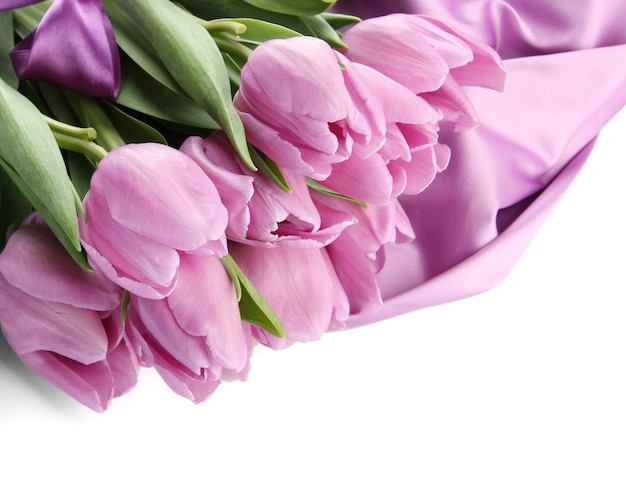 サテンの布に紫のチューリップの美しい花束、白