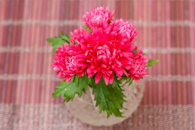 Красивый букет цветов красной астры в хрустальной вазе на деревянной салфетке. вид сверху.