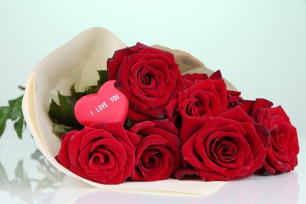 Красивый букет красных роз с валентинкой на зеленом фоне