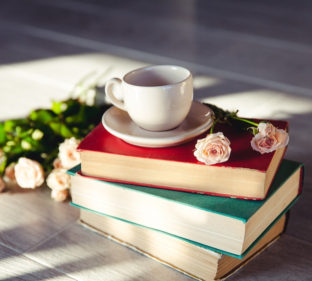 컵과 함께 책에 햇볕에 장미의 아름다운 꽃다발