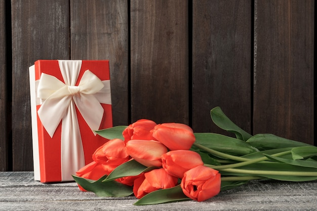 선물 상자와 함께 어두운 나무 테이블에 튤립의 아름 다운 꽃다발.