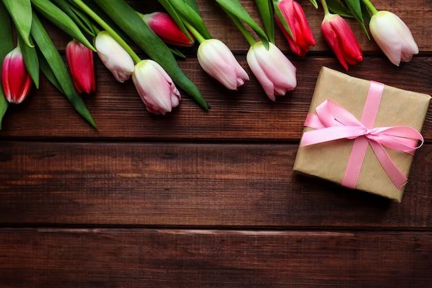ギフトボックスとコピースペースと暗い木製の背景にチューリップの美しい花束。グリーティングカード