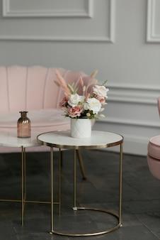 白とピンクの花の美しい花束がスタイリッシュなコーヒーテーブルの上に立っています