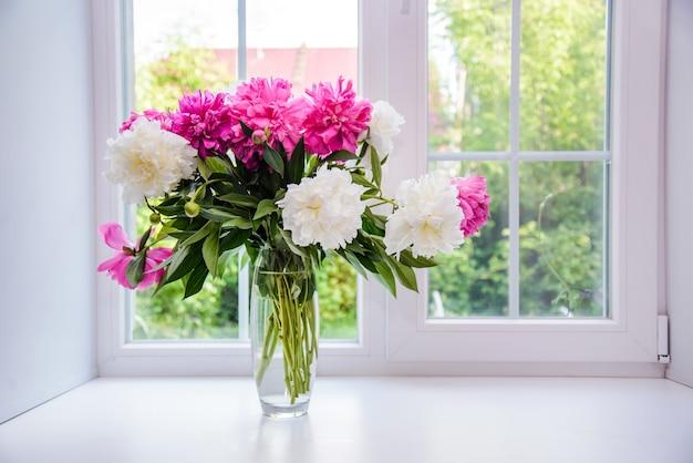 Красивый букет из белых и розовых пионов в вазе на подоконнике