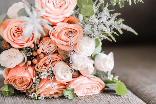 Красивый букет из белых и красных роз и серьги на нем как аксессуары невесты. горизонтальное фото