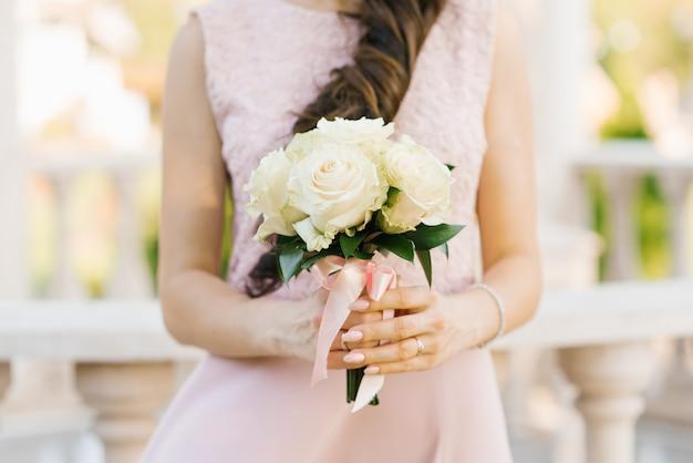 여자의 손에 흰색 또는 베이지 색 장미의 아름다운 꽃다발을 닫습니다