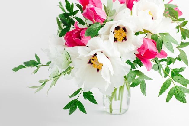 Красивый букет из белых пионов и розовых тюльпанов в стеклянной вазе на белом фоне