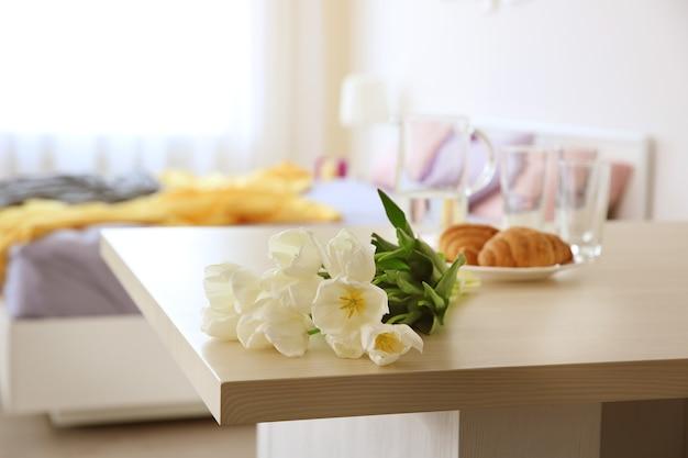 라이트 룸 테이블에 흰색 튤립과 크로와상의 아름다운 꽃다발