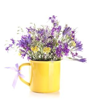 白で隔離されるカップで野生の花の美しい花束