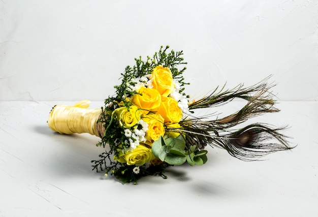 黄色いバラの孔雀の羽の美しい花束