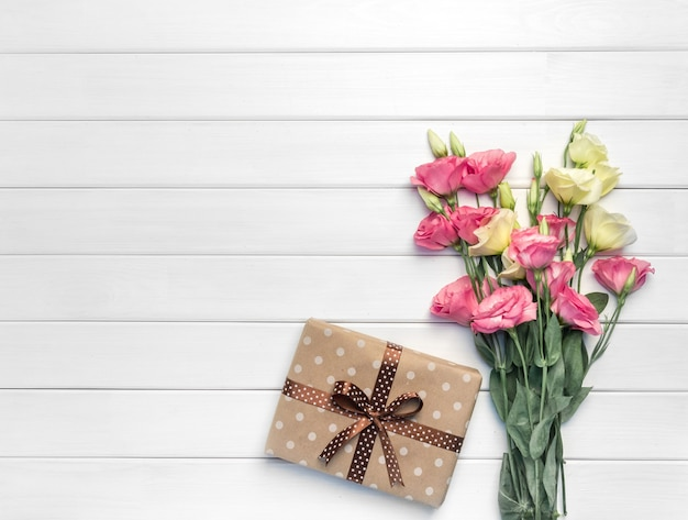 Beautiful bouquet of pink, purple, yellow eustoma flowers and handmade gift box on white wooden background. copy space, top view,