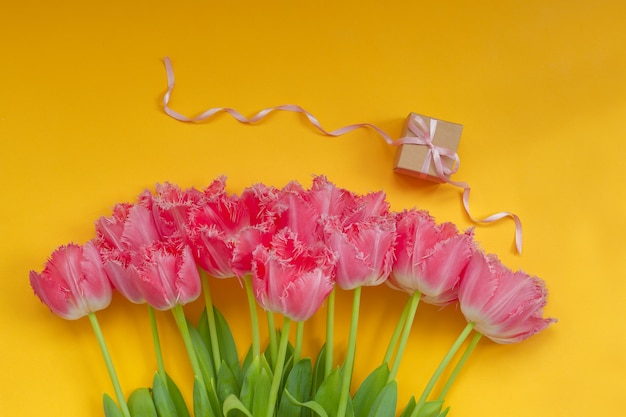 Beautiful bouquet of pink tulips flowers with present box on yellow surface