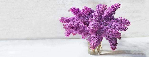 Beautiful bouquet of purple lilac on a glass jar ion white table