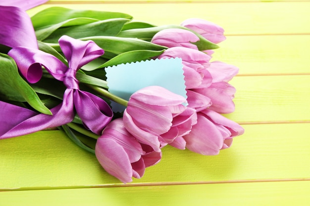 Beautiful bouquet of purple tulips on green wooden table