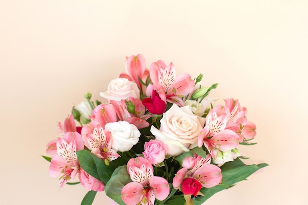 Beautiful bouquet of rose and alstroemeria flowers on light background.