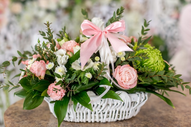 Beautiful bouquet of roses in white basket is on a table in flower boutique.