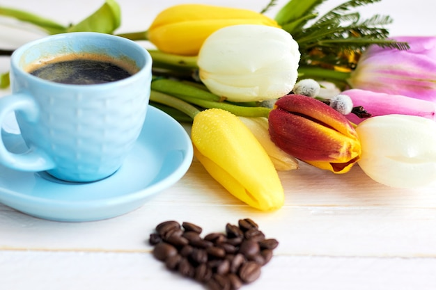Beautiful bouquet of spring flowers on light wooden surface with cup of morning coffee