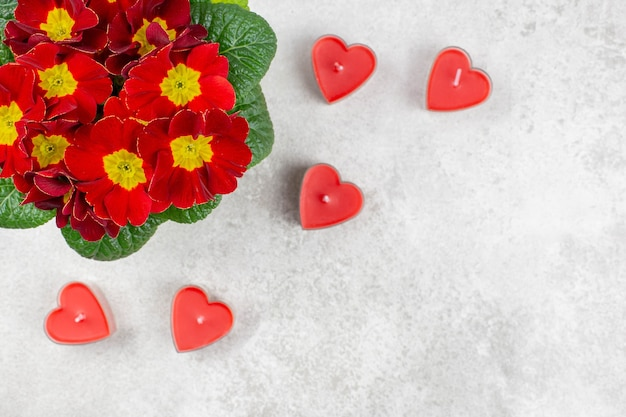 Beautiful bouquet of spring flowers and red candles in the form of a heart on gray concrete.