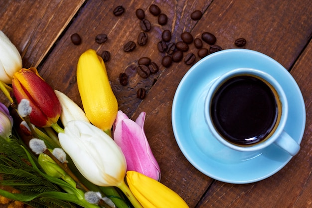 Beautiful bouquet of spring flowers on wooden surface with cup of morning coffee