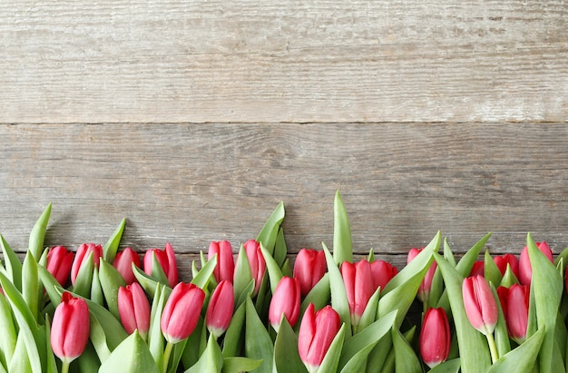Beautiful bouquet of tulips on wooden background
