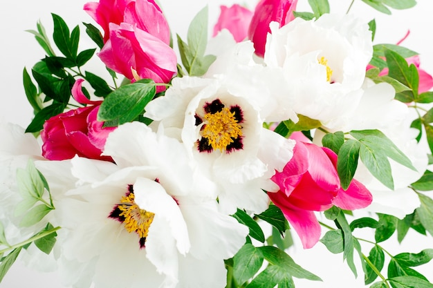 Beautiful bouquet of white peonies and pink tulips in a glass vase on a white background