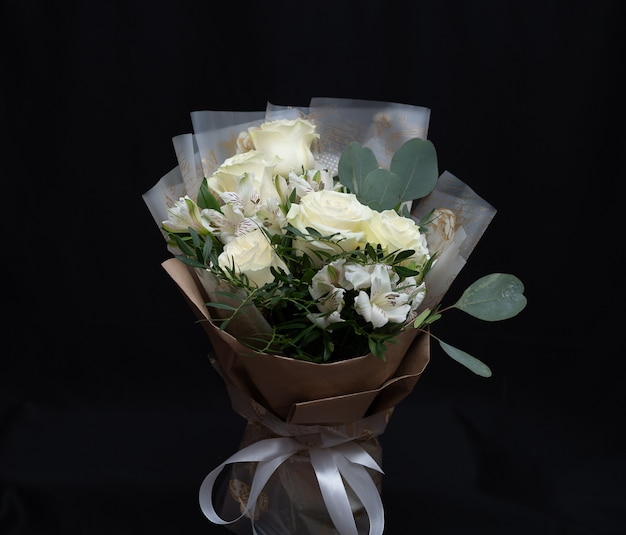 Beautiful bouquet of white roses, alstroemeria and lisianthus in kraft packaging on a black wall.