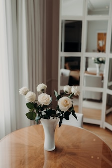 Beautiful bouquet of white roses in vace stands on wooden round table against cozy home interior