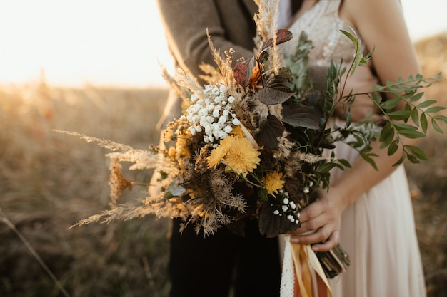 Beautiful bouquet of wild flowers in the hands of the bride