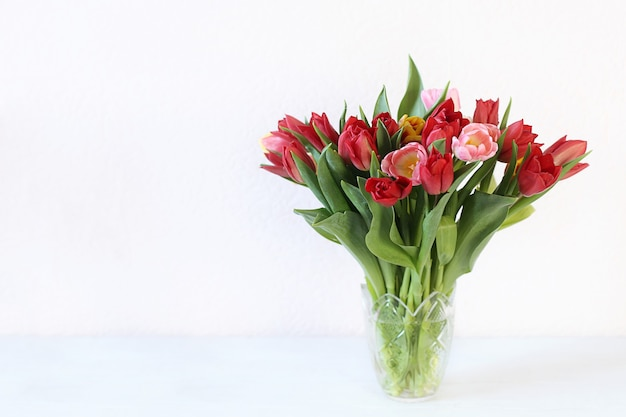 Beautiful bouquet with multicolored tulips in vase copy space