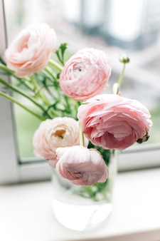 Beautiful bouquet with pink peonies flowers over the window
