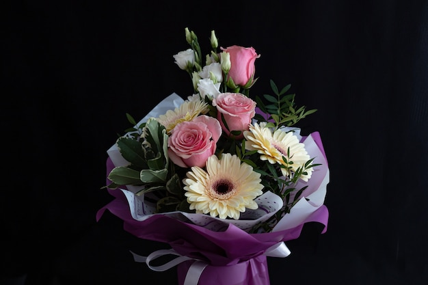 Beautiful bouquet with pink roses and gerberas on a black wall.
