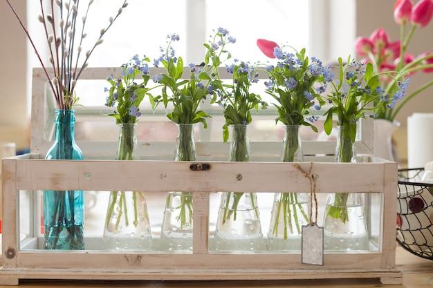 유리 화병에 있는 파란색과 분홍색의 아름다운 꽃다발은 가정 인테리어를 위한 봄 꽃입니다. 프리미엄 사진
