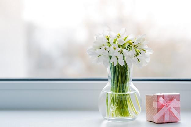 ピンクのギフトボックスと窓辺に春の太陽の光線でガラスのスノードロップの美しい花束。