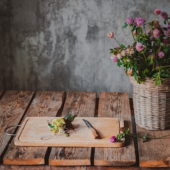 Beautiful bouquets of wildflowers wooden table cold concrete wall.